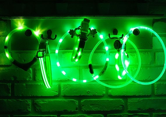 7 Different Green LED Dog Collars hanging up being tested for brightness