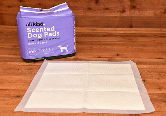 All kind scented pee pad for dogs laying flat on floor next to packaged product