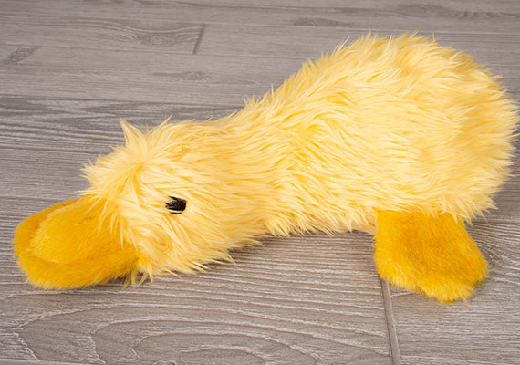 Bright yellow fluffy duckworth duck plush toy for dogs resting on wooden flooring