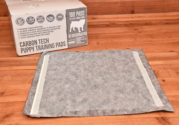 Bulldogology Carbon Tech Puppy Training pad laying flat next to box - winner of best premium pee pad for dogs