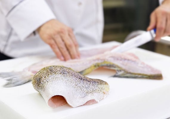 Chef removing skin from cod to be used in fish skin dog treats