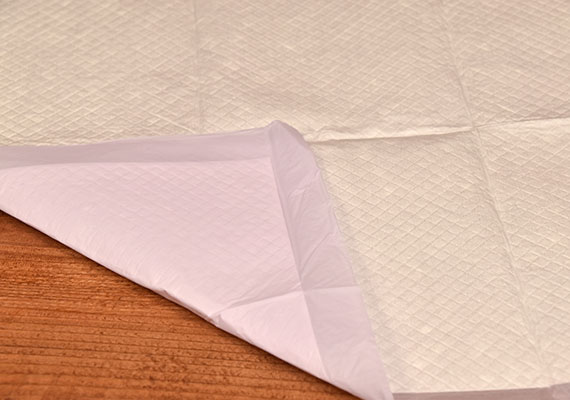 Corner of All Kind Pee Pads folded over to reveal plastic liner bottom - best scented pee pad for dogs winner