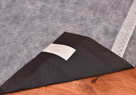 Corner of Bulldogology Carbon Tech Training Pad Folded over to reveal sticky tabs on plastic liner - winner of best premium pee pad for dogs