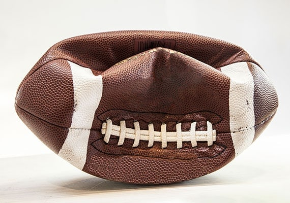 Deflated football that was punctured by sharp dog teeth