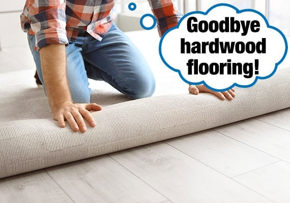 Man installing new flooring as he rolls out carpet to cover up slippery hardwood floor