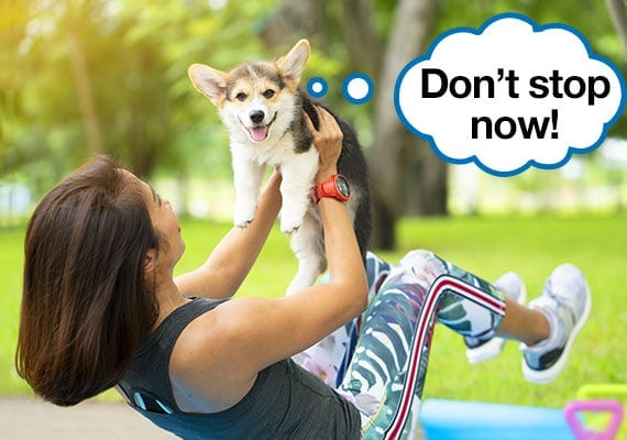 Woman doing abdominal crunch exercise while holding a corgi dog for extra weight