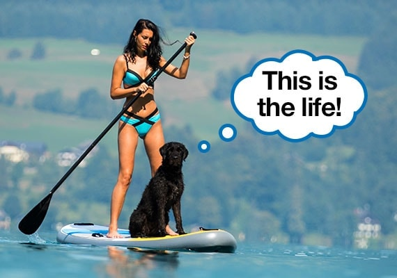 Woman exercising by paddleboarding across a lake with her black labrador sitting on paddleboard with her
