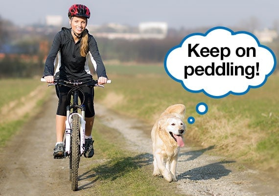 Woman exercising on bicycle while golden retriever runs alongside her on dirt path