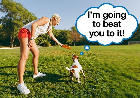 Woman throwing frisbee about to race her dog to retrieve it for exercise