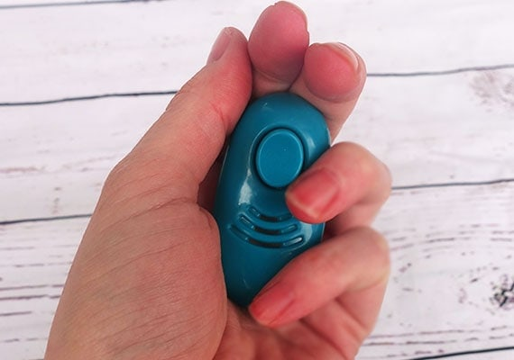 Soft dog training clicker held in palm of hand