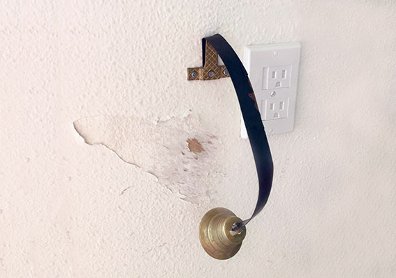 Wall behind dog doorbell that has been scratched by dog paws causing paint to peel with scuff marks